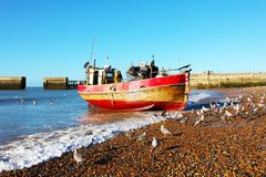 A fine red and gold Hastings fishing trawler comes ashore at Rock-a-Nore, Hastings, East Sussex, England. The crew prepare to off-load the fish catch and the royalty free stock photography