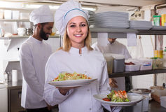 Crew of professional cooks working at restaurant Stock Image