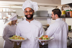 Crew of professional cooks working at restaurant Royalty Free Stock Photography
