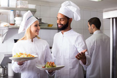 Crew of professional cooks working at restaurant Stock Photos