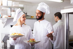 Crew of professional cooks working at restaurant Stock Images