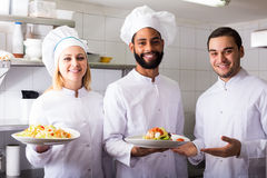 Crew of professional cooks working at restaurant Stock Photo