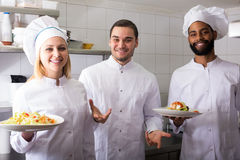 Crew of professional cooks working at restaurant Royalty Free Stock Images