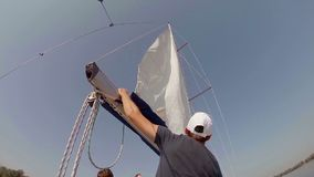 Crew putting sails up on a sailboat. Yachting, sailing, training. Stock footage stock footage