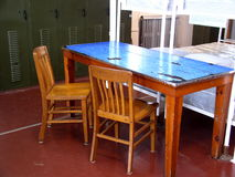Crew quarters table. This table in the crews quarters aboard ship offers limited space for personal use. Blue linoleum has suffered under innumerable card games stock photo