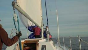 Crew raising sail on yacht, teamwork, friendship, support. Stock footage stock video