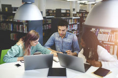 Crew of skilled male and female international students learning together. Preparing for examination in university library using modern technologies,group of Royalty Free Stock Photo