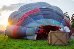 Crew at sunset prepare hot air balloon Royalty Free Stock Photo
