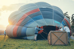 Crew at sunset prepare hot air balloon Royalty Free Stock Images