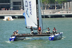 Crew of Team Aberdeen Singapore steering boat at Extreme Sailing Series Singapore 2013. Crew of Team Aberdeen Singapore led by skipper Scott Glen Sydney steering stock image
