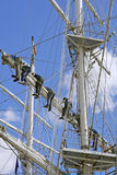 Crew Teamwork. Crew of the tall ship lowering sails Royalty Free Stock Image