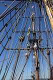 Crew unfurls a sail on a yardarm Royalty Free Stock Image