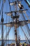 Crew unfurls a sail on a yardarm Royalty Free Stock Photography
