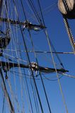 Crew unfurls a sail on a yardarm Royalty Free Stock Images