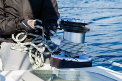 Crew work with genoa sheet rope and winch royalty free stock photography