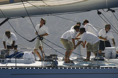 Crew Working On Sailboat. Side view of crew members working on sailboat stock photography