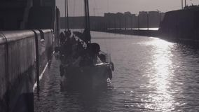 Crews of two yachts prepared to pass the gateway in the background of the city and under bright sun. stock video footage