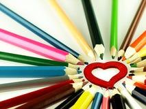 Creyones de madera coloridos y corazón rojo Imágenes de archivo libres de regalías