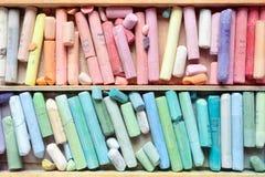 Creyones en colores pastel en primer de madera de la caja del artista Imágenes de archivo libres de regalías