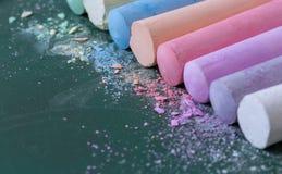 Creyones multicolores, en colores pastel Verde, amarillo, rosado, púrpura, azul Pasteles pintados Tiza derramada en un tablero ve Imágenes de archivo libres de regalías