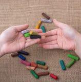 Creyones usados del color y manos de los adolescentes Imagen de archivo