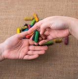 Creyones usados del color y manos de los adolescentes Imágenes de archivo libres de regalías