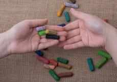 Creyones usados del color y manos de los adolescentes Foto de archivo libre de regalías