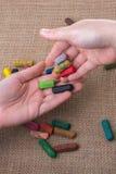 Creyones usados del color y manos de los adolescentes Imagenes de archivo