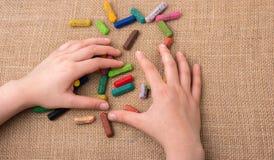 Creyones usados del color y una mano de los adolescentes Foto de archivo libre de regalías