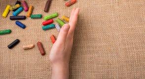 Creyones usados del color y una mano de los adolescentes Imagenes de archivo