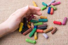 Creyones usados del color y una mano de los adolescentes Imagen de archivo
