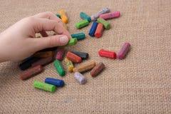 Creyones usados del color y una mano de los adolescentes Imágenes de archivo libres de regalías