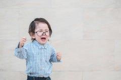 Cri asiatique triste d'enfant de plan rapproché parce qu'il veulent quelque chose sur le fond texturisé de marbre de mur en pierr photo libre de droits
