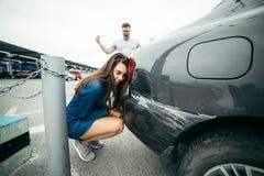 Cri d'homme sur la femme en raison de la voiture rayée images stock
