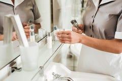 Criada joven del hotel que pone los accesorios del baño en un cuarto de baño Imagen de archivo
