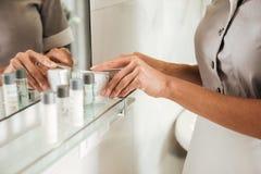 Criada joven del hotel que pone los accesorios del baño en un cuarto de baño Imágenes de archivo libres de regalías