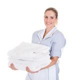 Criada joven feliz que sostiene las toallas imagen de archivo