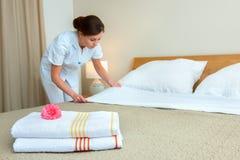 Criada que hace la cama en la habitación Imagen de archivo libre de regalías