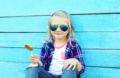 Criança à moda com o pirulito doce do caramelo sobre o azul colorido Fotografia de Stock Royalty Free
