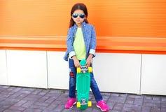 Criança à moda da menina com vestir do skate óculos de sol e camisa quadriculado Imagens de Stock