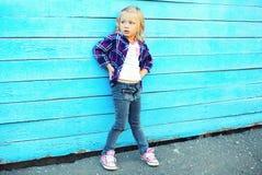 Criança à moda da menina na cidade sobre o azul colorido fotografia de stock