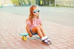 Criança à moda da menina que senta-se em óculos de sol vestindo do skate e na camisa quadriculado na cidade Fotografia de Stock