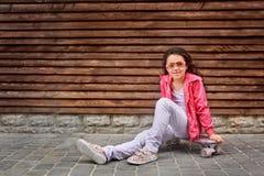 Criança à moda da menina que veste um revestimento cor-de-rosa do verão ou do outono, calças de brim brancas, óculos de sol fotos de stock