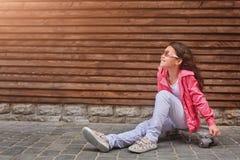 Criança à moda da menina que veste um revestimento cor-de-rosa do verão ou do outono, calças de brim brancas, óculos de sol fotos de stock royalty free