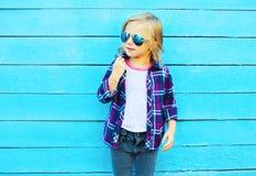 Criança à moda que levanta em um fundo de madeira azul foto de stock