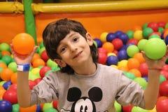 A criança é banhada nas bolas coloridas das crianças imagens de stock royalty free
