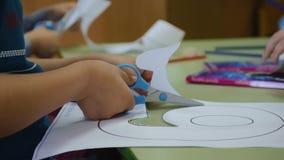 A criança é cortada do papel com figuras das tesouras As mãos da criança grandes Faculdade criadora do ` s das crian?as Pré-escol video estoque
