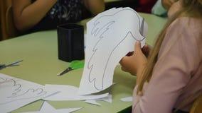 A criança é cortada do papel com figuras das tesouras As mãos da criança grandes Faculdade criadora do ` s das crian?as Pré-escol vídeos de arquivo