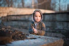 A criança é jogada por seixos em placas concretas velhas Fotografia de Stock