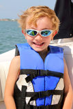 Criança 6yr idosa loura com revestimento de vida & vidros de sol imagem de stock